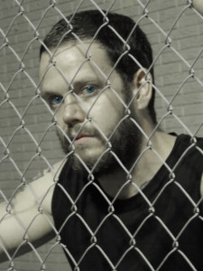 Profile picture of Adam behind a chain link fence